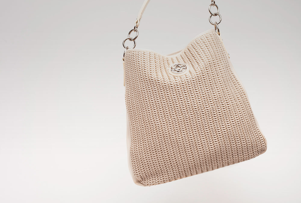 lovve wendy woven bag hangs into frame at an angle in front of a grey background