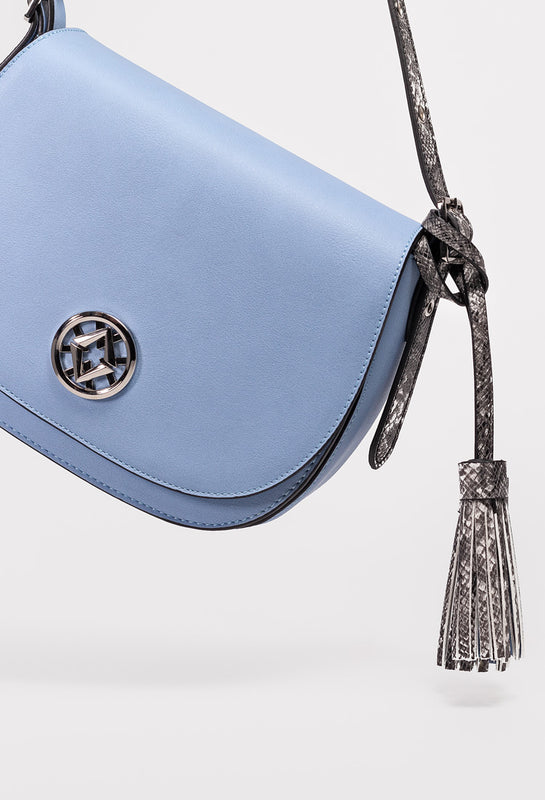 lovve blue tonya tassel bag hangs at an angle in front of a grey background