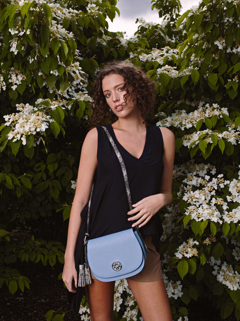 tonya tassel in blue is worn by a model in front of flowering plants