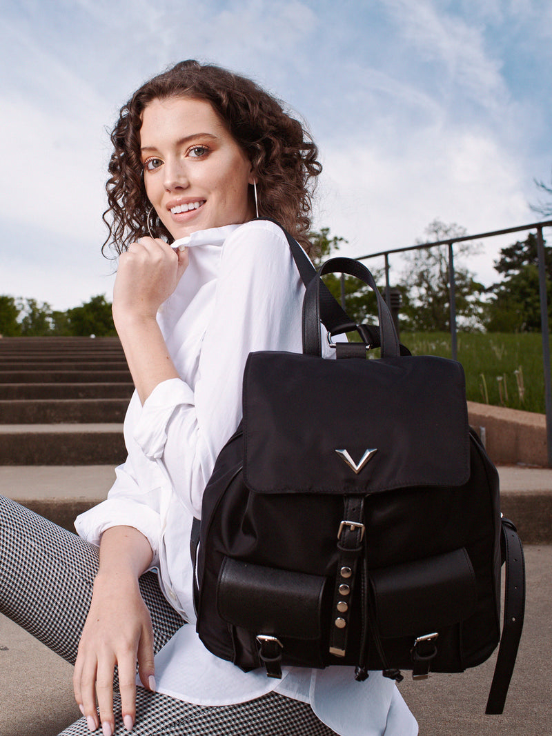 Lovve brandy backpack worn by model who is sitting on concrete steps
