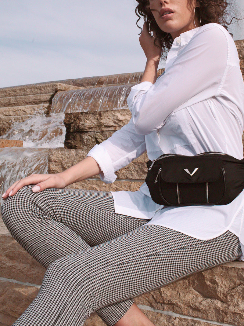 Lovve bethany belt bag on model in front of running water