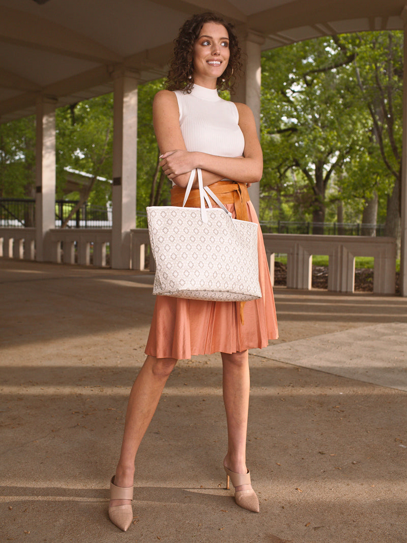 A model for the LoVvé handbag line stands in a peach colored skirt in front of concrete pillars with the LoVvé signature tote