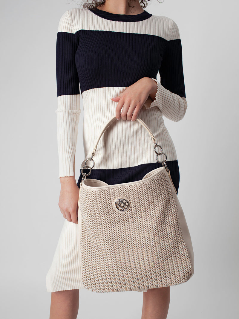 "Lovve bag ""wendy woven"" in nude is shown draping from a models hand"