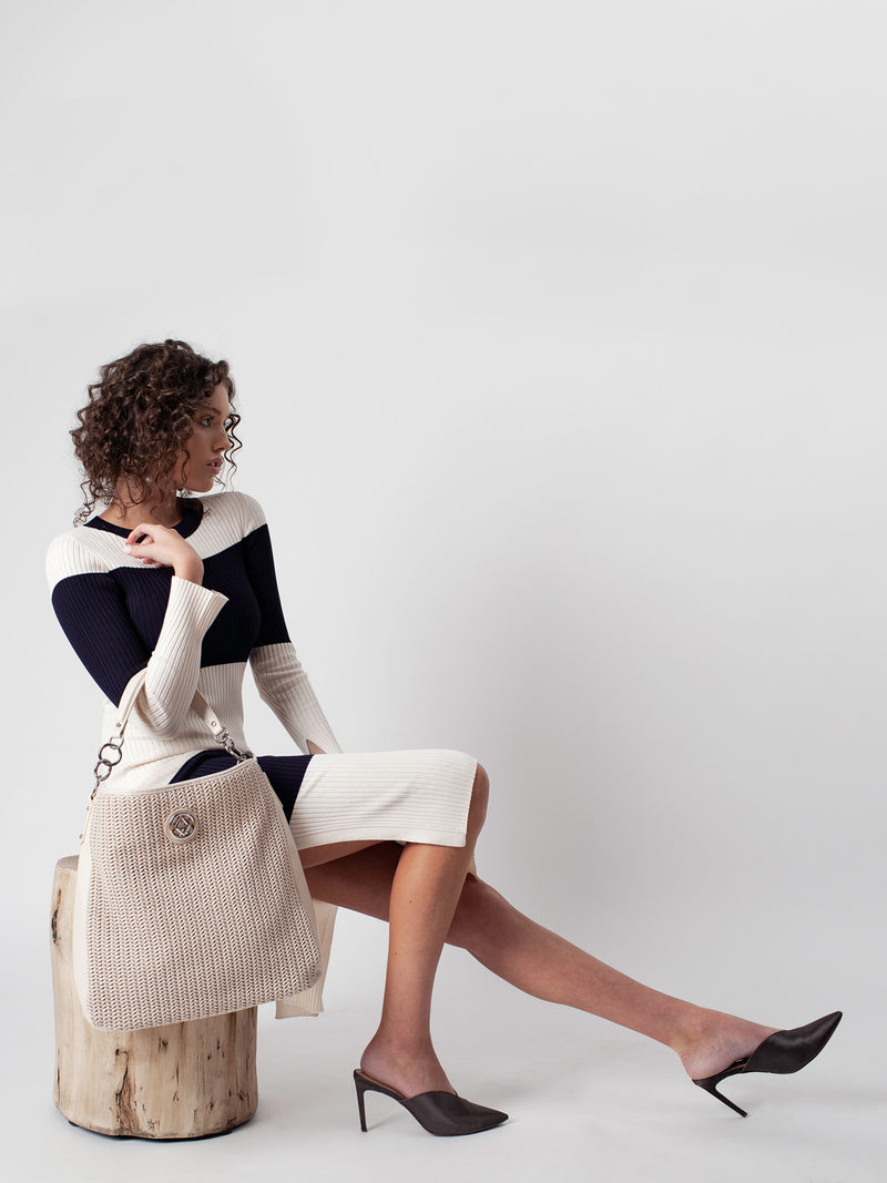 "Lovve bag ""wendy woven"" in nude is worn by a model sitting on a stump"