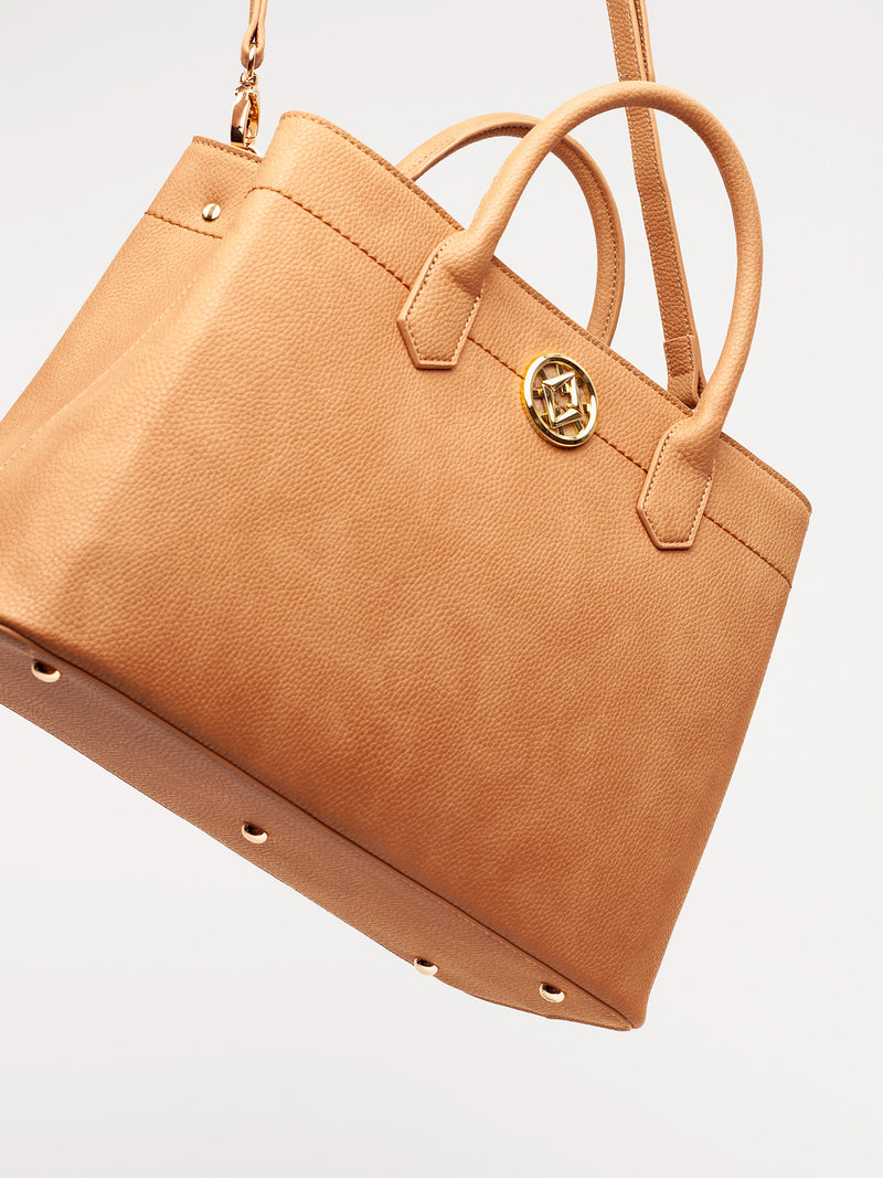 Lovve camel colored cassy satchel bag hanging at an angle in frame