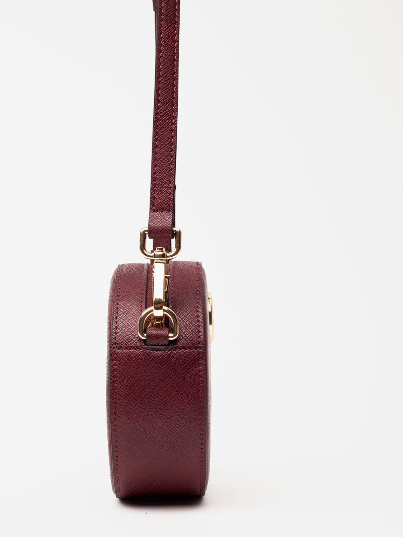 Lovve burgundy olivia oval bag hangs in frame and is shot from the site