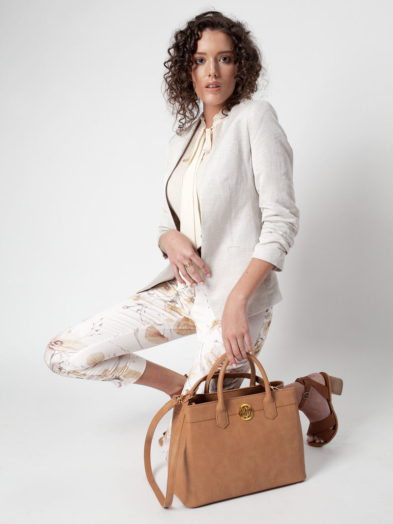 Lovve camel colored cassy satchel bag is being carried by a model in front of a grey background