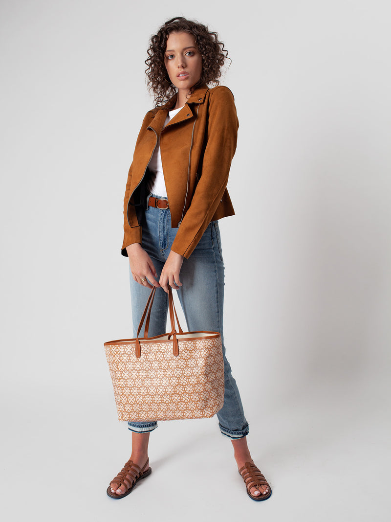 Love signature print tote is being carried by a model in front of a grey background.