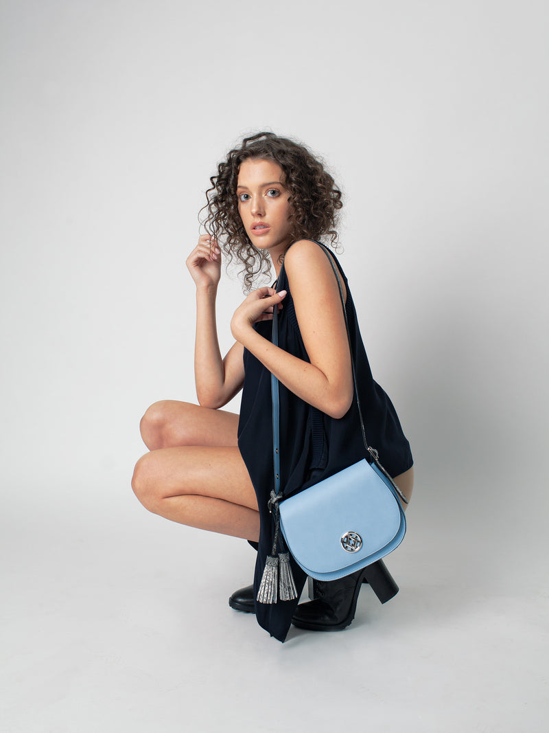 tonya tassel in blue is worn by a model that crouches down in front of a grey background