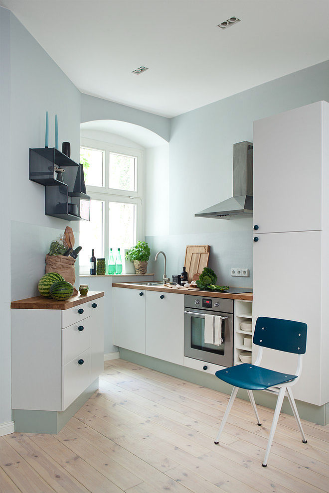 the kitchen makes the most of a tight angled space by a window once again it is super practical with a warm cozy feel that inspires simplicity