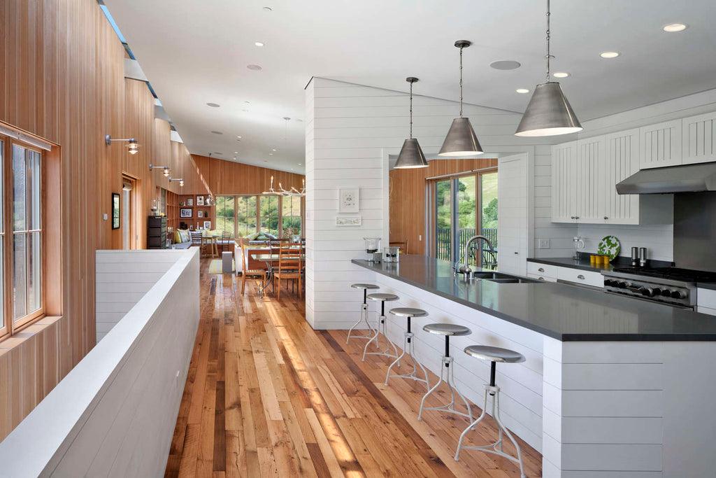 the white wooden planks make a nice transition from the rest of the house to its heart the kitchen it seats up to 16 people comfortably for festive