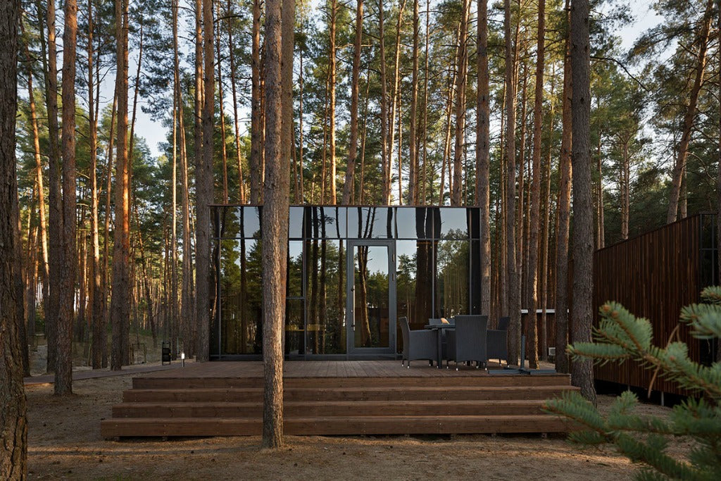 the design carefully considers the relationship between the structures and the forest outside making it appear as though it
