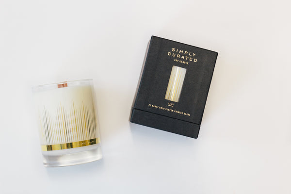 Amber Cardamom soy wax candle with crackling wooden wick in gold cocktail glass. Black gift box with gold foil and window.