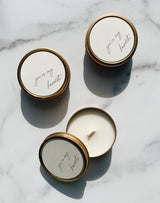 three gold soy wax travel candle tins with wooden wicks and you're my favorite on the neutral label in cursive. Harsh shadows on the product image in natural light.