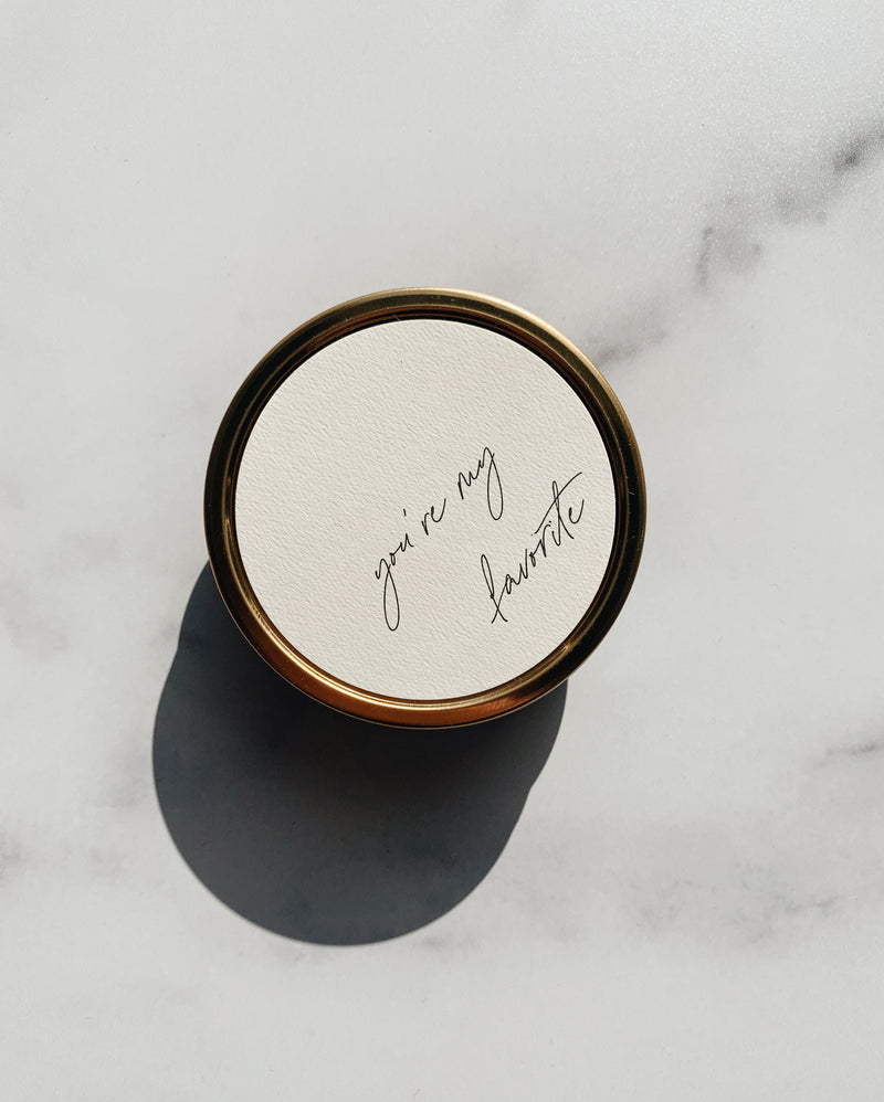 100% soy wax travel candle in gold tin with wooden wicks and you're my favorite on the neutral label in cursive. Harsh shadow on the product image in natural light.