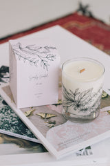 eucalyptus basil star jasmine soy candle with botanical illustration on the glass with a crackling wooden wick and a blush gift box on top of magazines