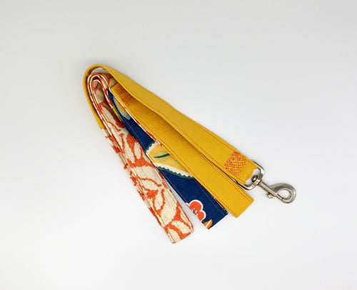 Patchwork dog leash in shades of blue, yellow, and orange patterned canvas.