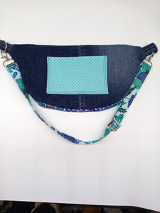 Rear view of blue, teal, and denim fanny pack with pocket.