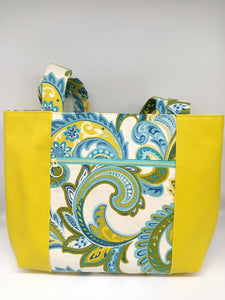 Front view of canvas and vinyl tote bag in blue and green paisley print canvas and yellow vinyl