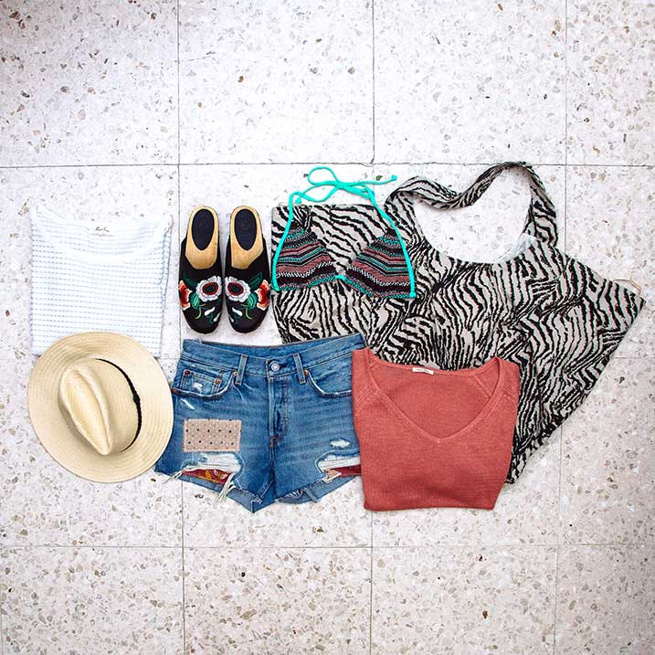 Denim shorts, clogs, beach bag and a sun hat are all essential items for a Holiday Capsule Wardrobe