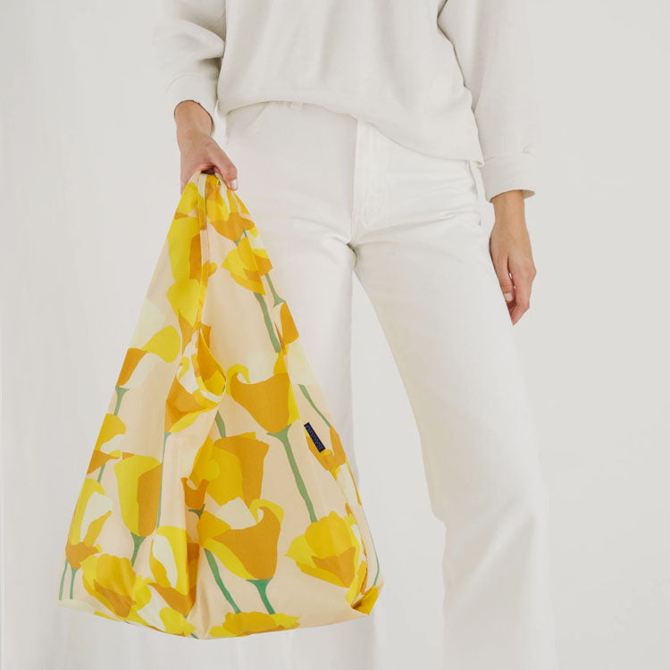 Model holding a Baggu Golden Poppy Reusable Bag