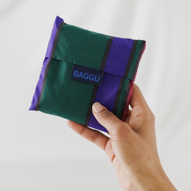 Baggu Scarf Stripe Reusable Bag folded into its carry pouch