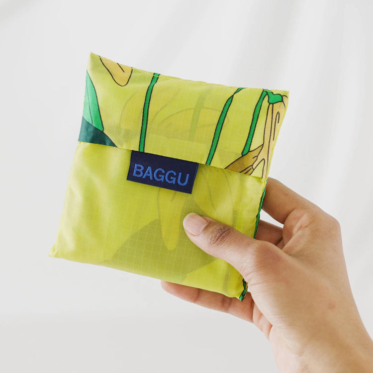 Baggu Yellow Lilly Reusable Bag folded into its carry pouch