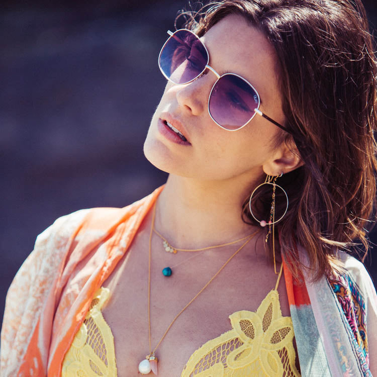 Lifestyle shot of model wearing Wanderlust Life Globe Large Hoop Pink Opal Earrings