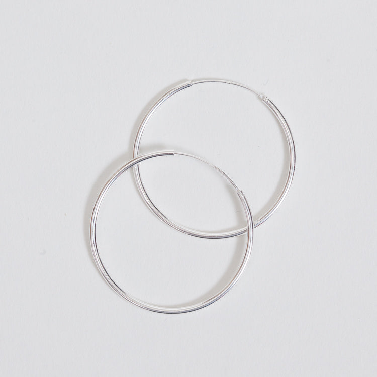 Product shot of the Pernille Corydon Midi Plain Silver Hoop Earrings