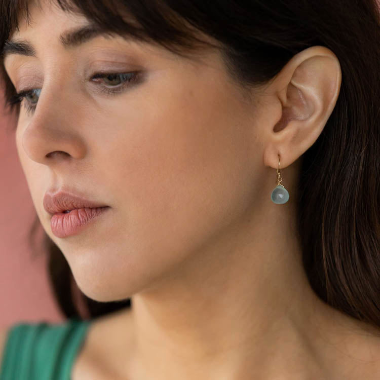 Model wearing a pair of Wanderlust Life Sea Glass Chalcedony Isla Drop Earrings