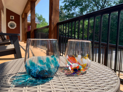 An Ocean Wave and Multi hand blown wine glass rest on a patio table.