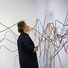 Image of MiAL Artist looking at paper and wires on a wall creating an installation
