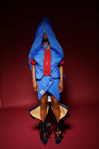 Cobalt blue coat and skirt sleeping bag 'onesie' with added hood and dropped hem skirt with red zipper detailing. Can be used as a sleeping bag and re-purposed outfit. Piece by Amber Kim