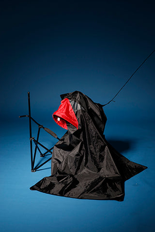 Photograph of tent black sculpture with red hood and blue background with broken camping chair. Contemplating the festival waste. By Amber Kim