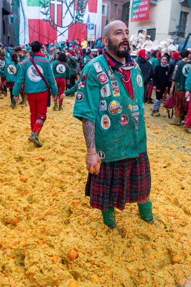 Image set in Spanish orange throwing festival: Gentleman in red tartan skirt, teal green top covered in fabric badges, standing among orange leftovers- he is the orange thrower. Artwork by Andrea Capello