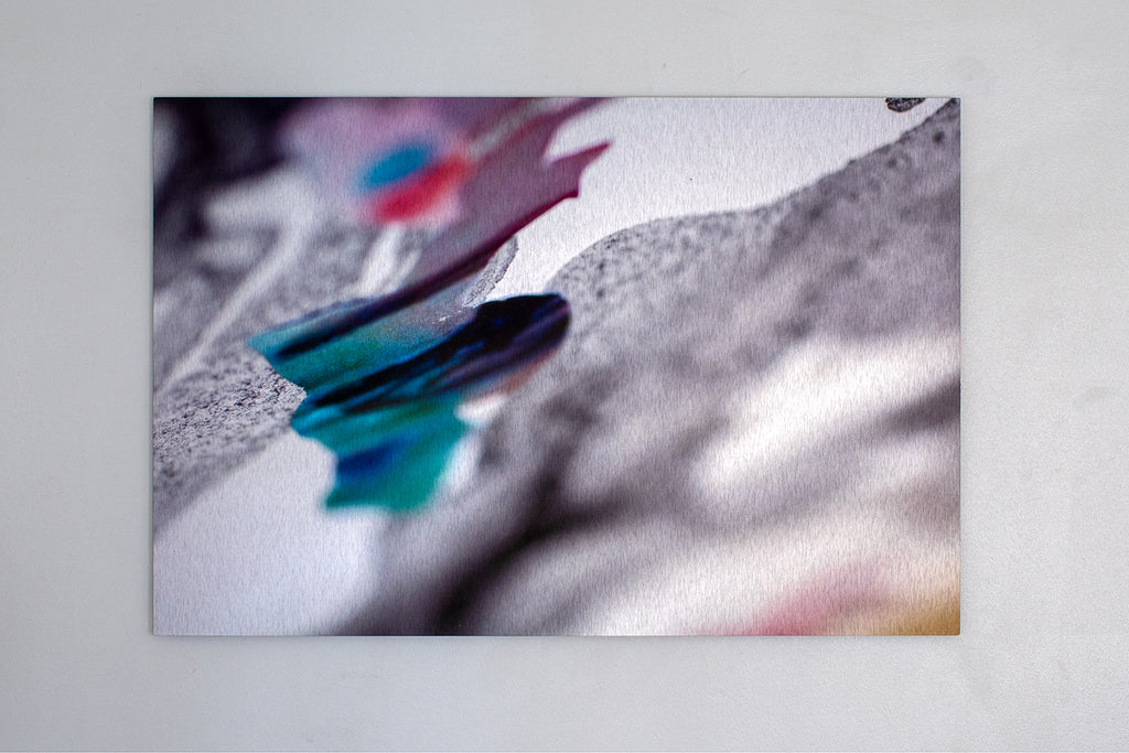 Wall-mounted aluminium print of an abstracted, textured surface with black, purple and blue inks. Piece by Danielle Jacques