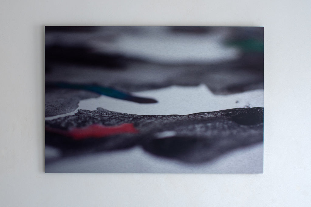 Wall-mounted aluminium print of an abstracted, textured surface with black, red and green inks. Piece by Danielle Jacques