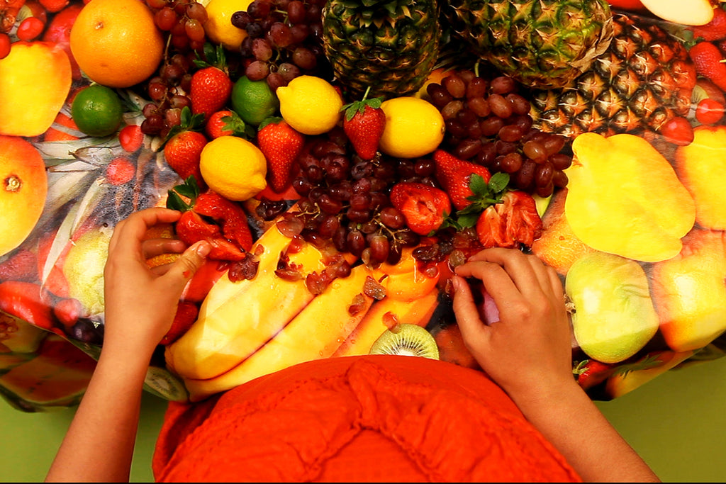 A photograph of a table covered in bright fruits. There are strawberries, limes, pineapples, grapefruits and grapes. There is an upper torso of a person wearing orange with their forearms and hands showing holding some of the fruit. By Gabrielle Brooks.