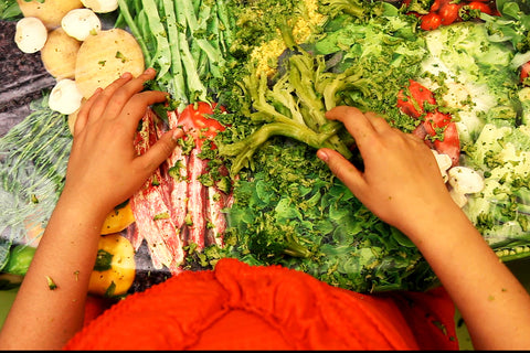 This is a photograph of a bright table with colourful vegetables on the top. There are some beans and bright green broccoli There is the upper torso of a person in bright orange.  There is also a pair of hands visible that are holding some of the broccoli.  By Gabrielle Brooks.