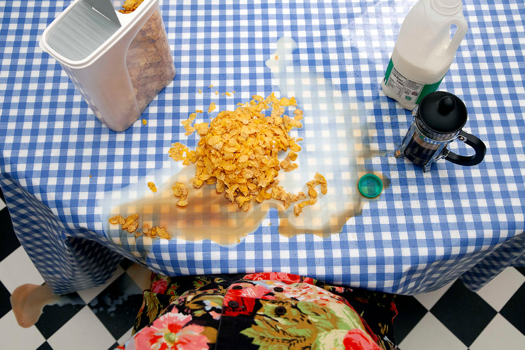This is a photograph that depicts a table in a white and blue table cloth. On top of the table there is a plastic bottle of milk, a cafetiere with coffee, a plastic box of cereal. In the middle of the table there is a pile of cereal and some spilled milk and coffee. The torso of a person is visible in a floral top. By Gabrielle Brooks.