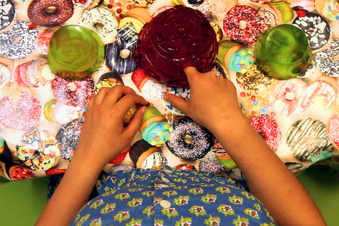 This photograph is of a kitchen table with a brightly coloured table cloth with printed cakes and doughnuts. On top of the table are three jelly pots, two green on the side and a dark purple bigger on in the middle. There is a visible torso of a person visible with the hands on the table. One of the hands is close to the purple jelly form with a finger poking through it. By Gabrielle Brooks.