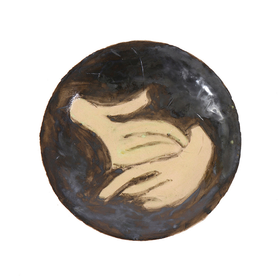 A small brown plate displaying a pair of pale cupped hands upon black leather glaze.