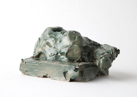 Hand-made glazed stoneware reclining jade figure, which lays across its plinth. By Henry Glover.