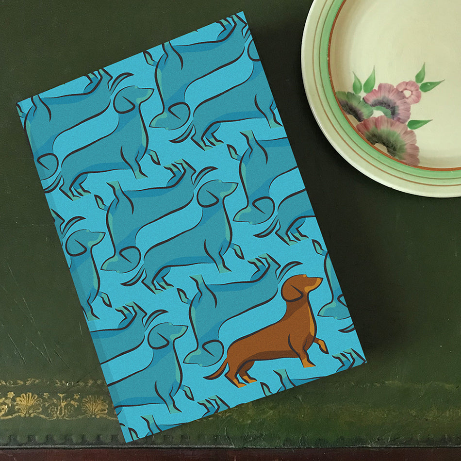Cyan blue background notebook with dachshund print and upside down print with statement brown dachshund. By Lydia Jones