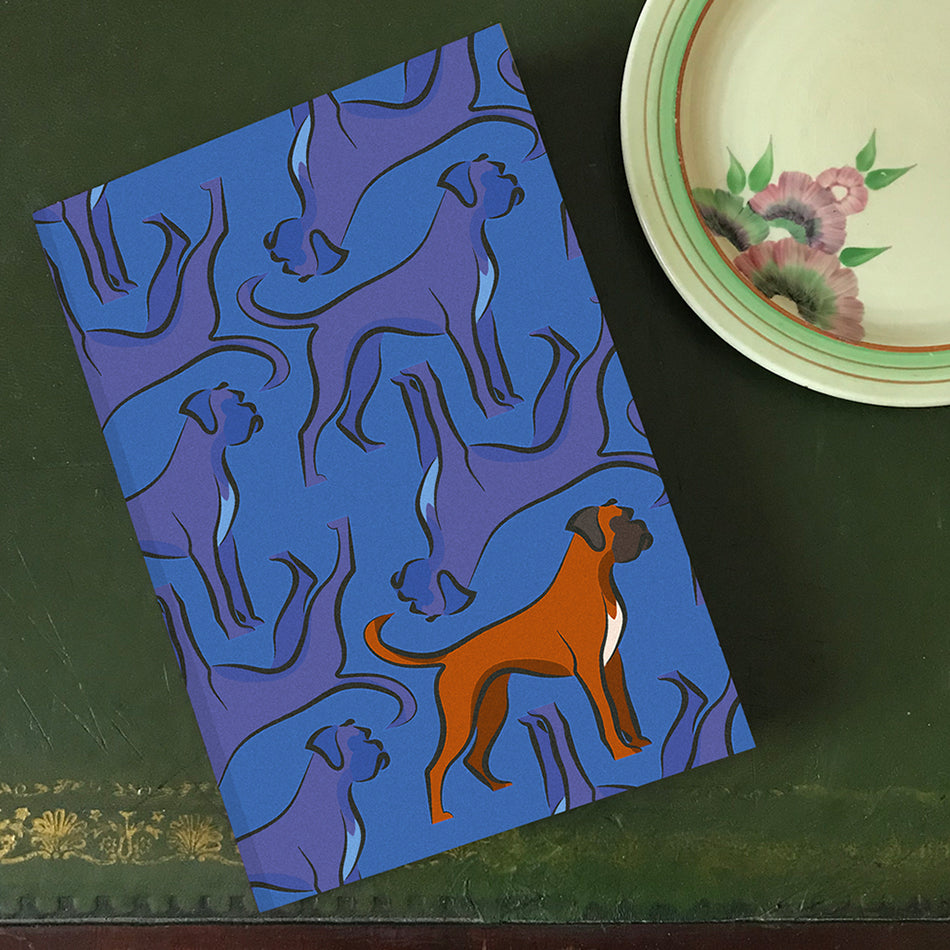 Blue tonal background on notebook with violet Billy the Boxer dog print, with upside down dogs and statement brown boxer. By Lydia Jones