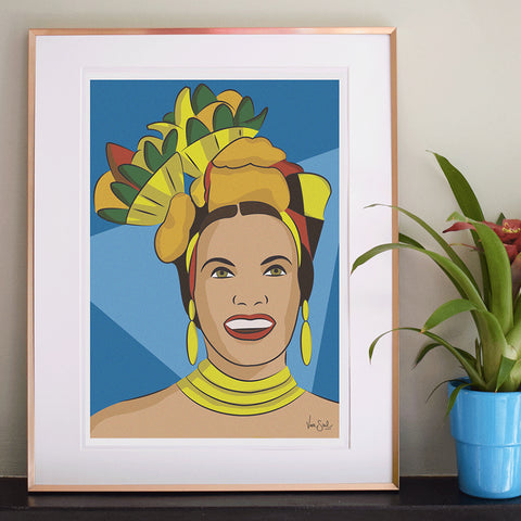Image of 'Carmen' print on shelf with potted plant. Carmen print has blue tonal background, a digital print of Carmen wearing a fruit styled carnival headpiece. Lots of yellow detailing contrasts the tonal blue background. By Lydia Jones