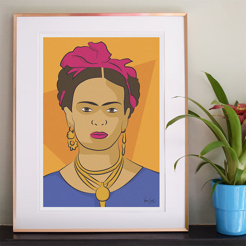 Image of 'Frida' print on shelf with potted plant beside it. 'Frida' image of heavily jeweled Frida in Digital Print form with large pink hair tie. By Lydia Jones