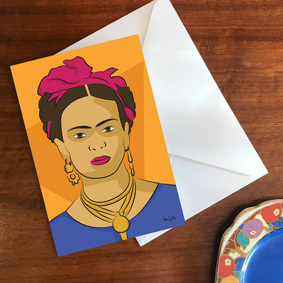 Image of 'Frida' greeting card on wooden background. Greeting card has digital print of 'Frida' on orange tonal background. By Lydia Jones