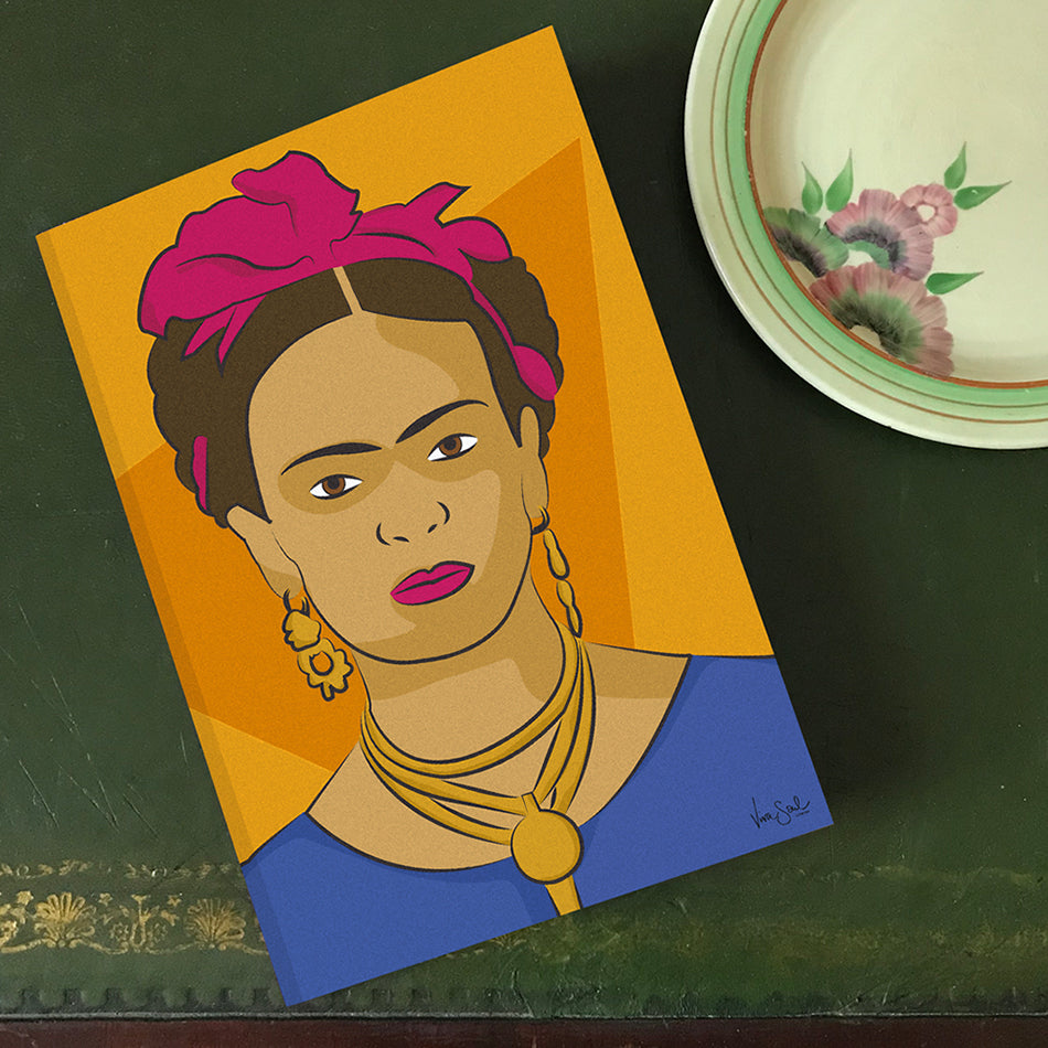 Image of 'Frida' notebook: tonal orange background with contrast pink hair tie and blue top. By Lydia Jones