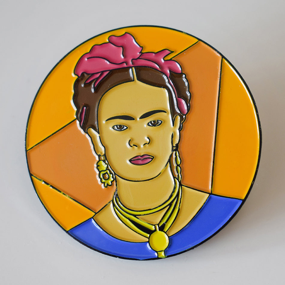 An enamel pin badge with a female portrait on it. The portrait is of Frida Kahlo on an orange background. By Lydia Jones.
